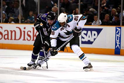 San Jose Sharks right wing Mike Grier stickhandles around an opponent