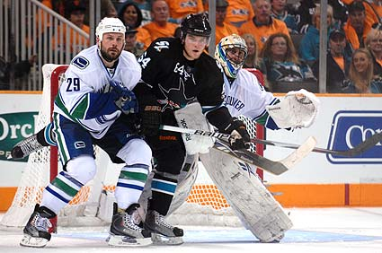 Jamie McGinn battles Aaron Rome in front of Vancouver net in second period